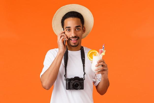 Toerisme, reizen en resort concept. afro-amerikaanse vrolijke man op vakantie, met drankje