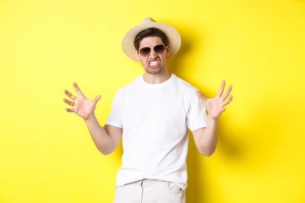 Toerisme, reizen en vakantie concept. brutale jongeman op vakantie, iets groots en op elkaar klemde tanden, staande in zonnebril en zomerhoed.