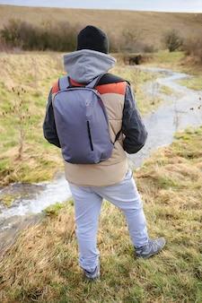 Toerisme. reiziger met een rugzak kijkt naar de stroom. wandelen