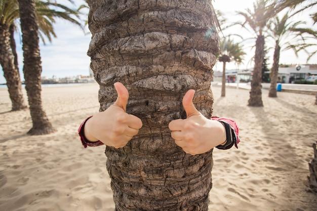 Toerisme, zomervakantie en reisconcept - een gebaar van duim teken omhoog tegen de palmboom.