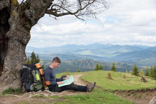 Toerist bestudeert een kaart van het gebied onder een boom langs de weg