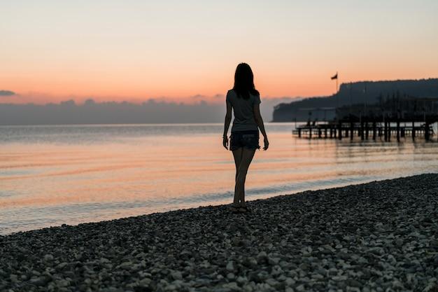 Toerist bij de zonsopgang die op de kustlijn loopt