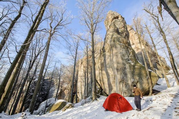 Toerist dichtbij de rode tent in de bergen