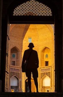 Toerist dichtbij oud historisch gebouw in oezbekistan