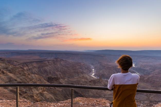 Toerist die de canion van de vissenrivier, toneelreisbestemming bekijken in zuidelijk namibië. ultra brede hoekmening van hierboven, kleurrijke schilderachtige zonsondergang.