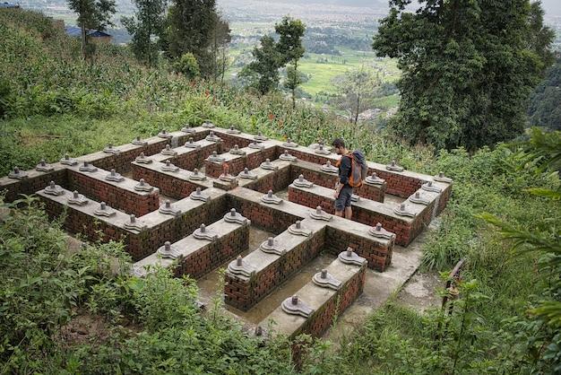 Toerist die door een tuin loopt in de vorm van een swastika en monolieten shiva lingam en yoni (shivalingam). nepal
