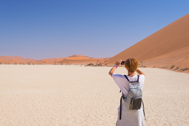 Toerist die foto met slimme telefoon nemen in sossusvlei, namib-woestijn, het nationale park van namib naukluft.
