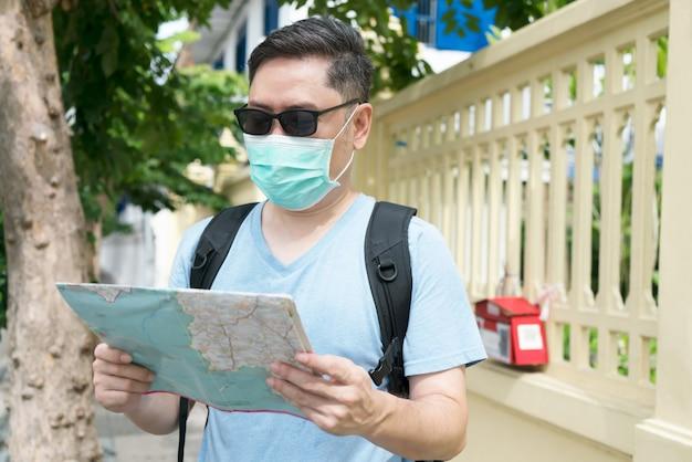 Toerist die gezondheidsmaskers draagt en kaart voor reisplanning houdt