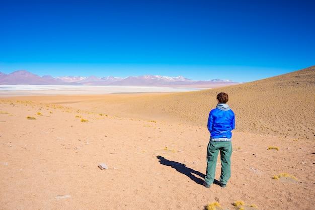 Toerist die het overweldigende landschap van zout bevroren meer op de andes bekijkt