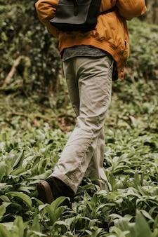 Toerist die in het bos achteruitkijkt wandelen