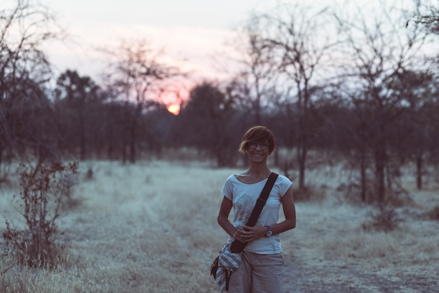 Toerist die in het struik en acaciabosje bij zonsondergang lopen, bushmandland, namibië.