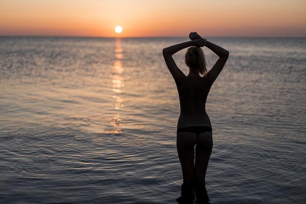 Toerist die in zwempak op de zonsopgang let