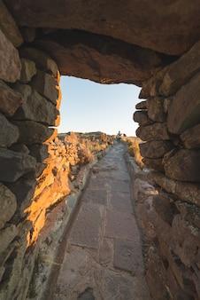 Toerist die inca-paden verkennen bij zonsondergang op het eiland amantani, het titicacameer, een van de meest schilderachtige reisbestemmingen in peru. reisavonturen en vakanties in amerika.