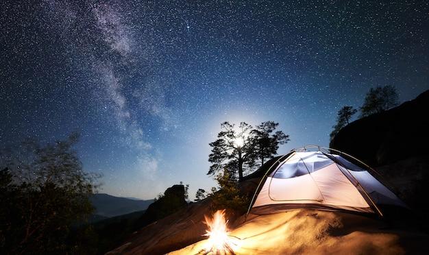 Toerist die op rotsachtige berg onder nacht sterrige hemel kampeert