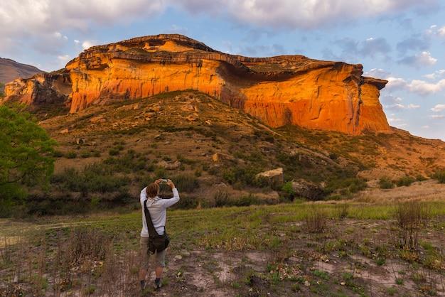 Toerist die slimme telefoon houden en foto nemen bij toneelklip die door zonsonderganglicht wordt verlicht in het majestueuze nationale park van golden gatehooglanden, beroemde reisbestemming in zuid-afrika.