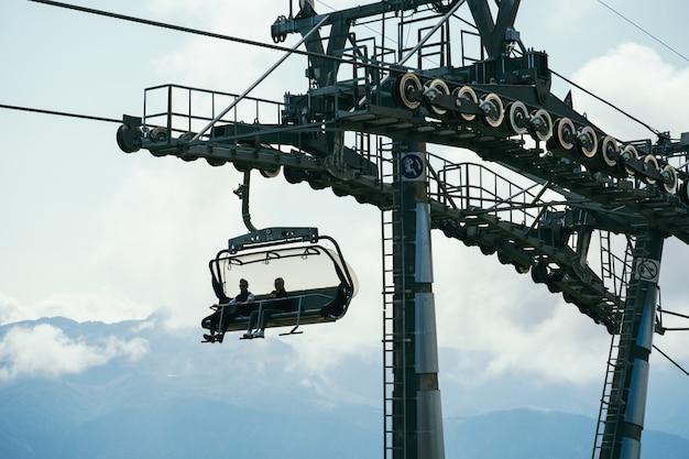Toerist die zich in de kabelbaan op een vage achtergrond van hoge bergen in blauwe nevel in de ochtend beweegt