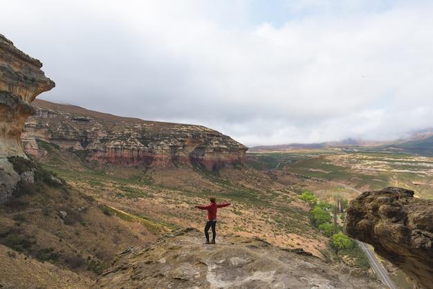 Toerist die zich met uitgestrekte wapens bevindt en het panorama in het majestueuze nationale park van golden gatehooglanden bekijkt, reisbestemming in zuid-afrika. avontuur en reizende mensen.
