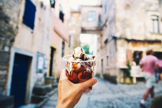 Toerist houdt in de hand fritule donuts ballen met chocolade zelfgemaakte beignets