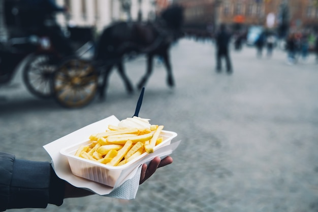 Toerist houdt populaire straat junkfood franse frietjes in holland amsterdam nederland