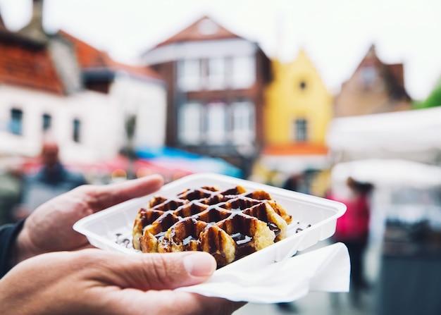 Toerist houdt populaire straatvoedsel belgische smakelijke wafel met chocoladesaus in de hand