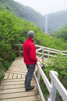 Toerist in een rode jas kijken naar een waterval in ijsland