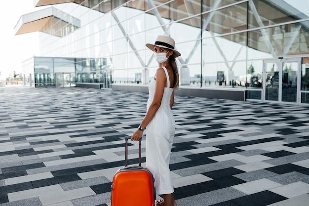 Toerist in gek masker dat zich dichtbij luchthavengebouw bevindt