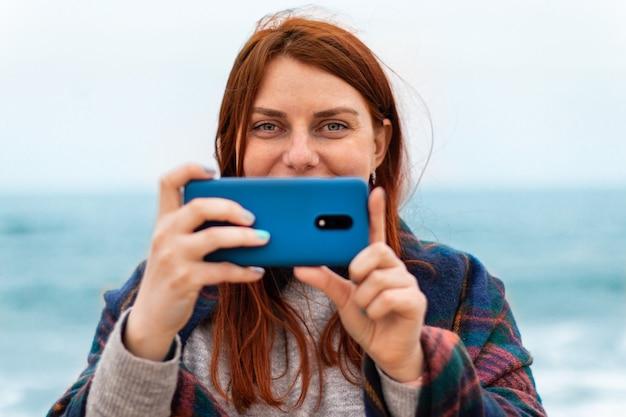 Toerist kaukasisch rood haar meisje maakt foto's of video-opname op smartphone op het strand in de buurt van de oceaan