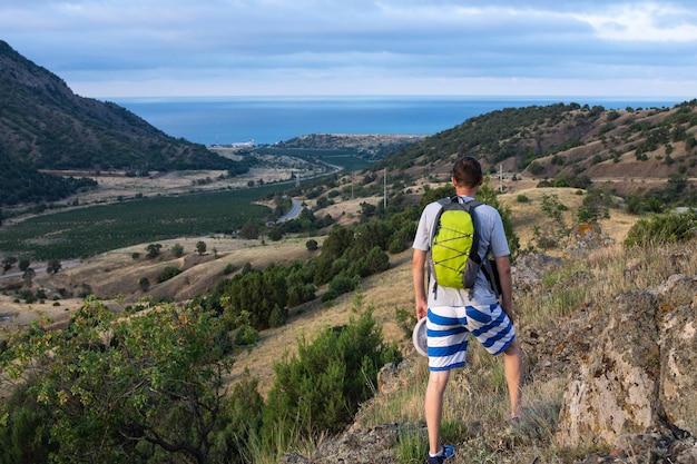 Toerist kijkt naar de zee en de vallei met wijngaarden