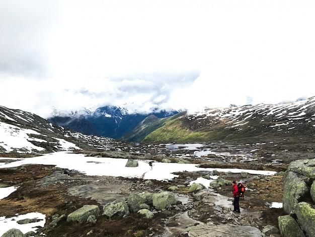 Toerist loopt over de sneeuw in de bergen
