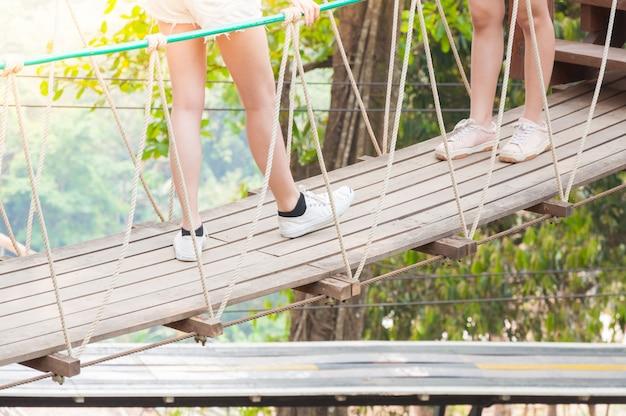 Toerist loopt weg op een houten hangbrug, steek over naar het bos aan de andere kant