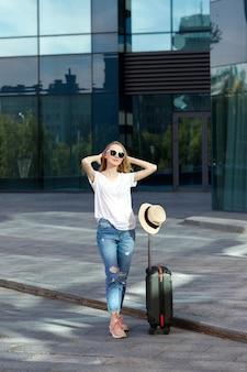Toerist met bagage in de zon tijdens de reis op de achtergrond van de luchthaven