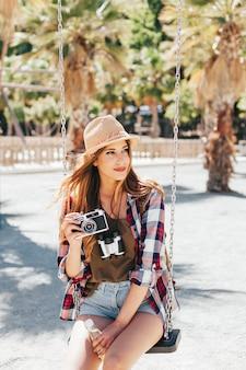 Toerist met camera op de schommel