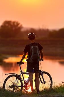 Toerist met een fiets op de zonsondergang achtergrond.