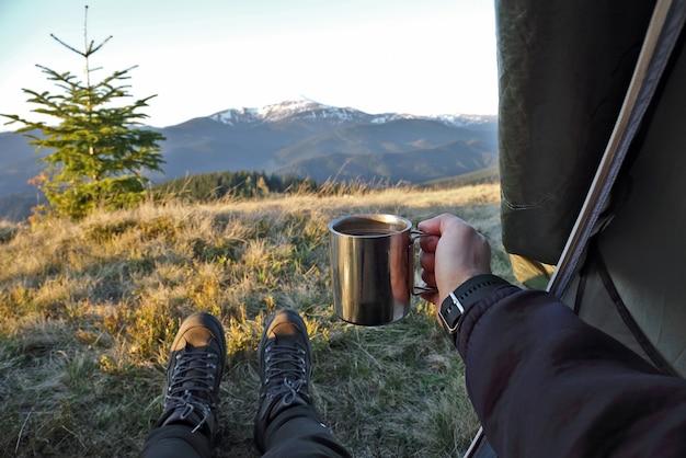 Toerist met een kopje koffie in tent met uitzicht op de bergen