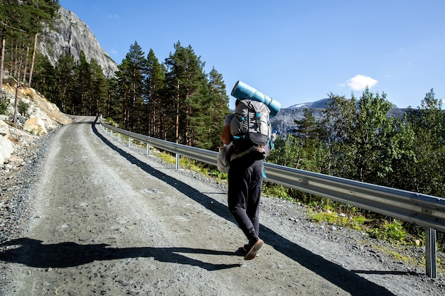 Toerist met een rugzak loopt langs een onverharde weg