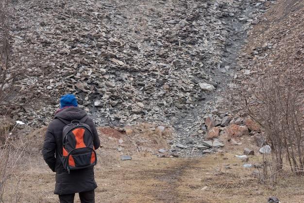 Toerist met een rugzak op de achtergrond van de textuur van de stenen van een industriële locatie.