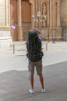 Toerist met een rugzak op straat fotografeert het achteraanzicht van de kathedraal