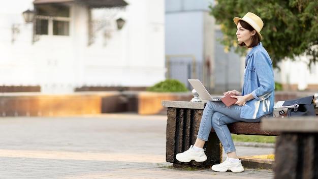 Toerist met hoed zittend op een bankje buitenshuis