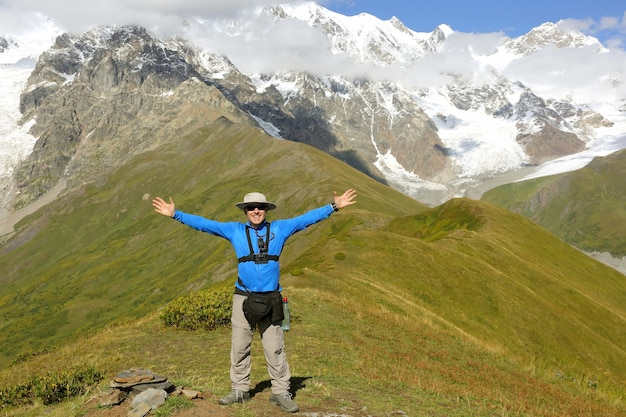 Toerist met opgeheven armen staande tegen een berglandschap