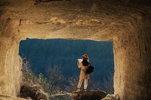 Toerist met rugzak en papieren kaart die bergketen en dennenbos bewondert tijdens de reis
