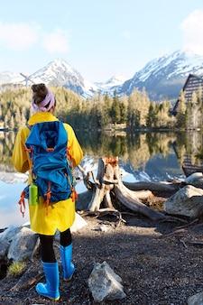 Toerist met rugzak staat in de buurt van bergrivier, geniet van wilde natuur met prachtig uitzicht, draagt gele lange anorak