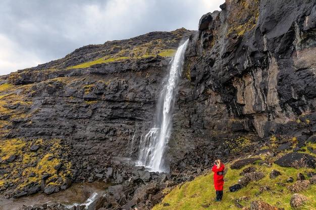 Toerist neemt een foto van de fossa-waterval op het eiland streymoy op de faeröer