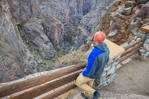 Toerist op de granieten kliffen van de black canyon of the gunnison, colorado, usa