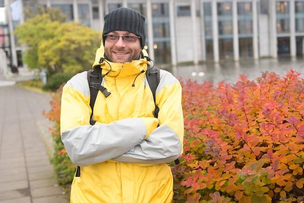 Toerist op stedelijke achtergrond. man toeristen dragen warme beschermende kleding voor koude klimatologische omstandigheden. toeristische reiziger concept. toerist goed materiaal klaar om scandinavisch of noords land te verkennen.