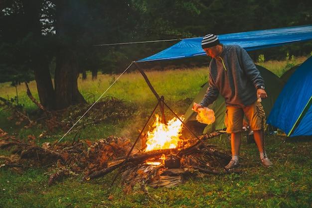 Toerist steekt vuur aan. reiziger steekt vuur aan in kamp. man bij kampvuur.