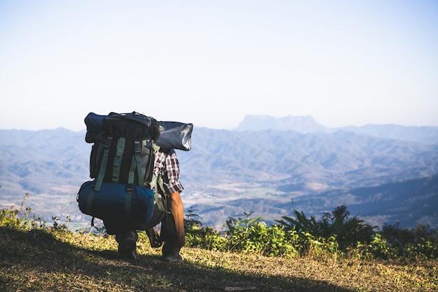 Toerist vanaf bergtop. zonnestralen. man draagt grote rugzak tegen zonlicht