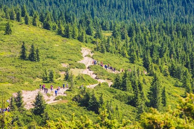 Toeristen beklimmen de berg langs een rotsachtig pad