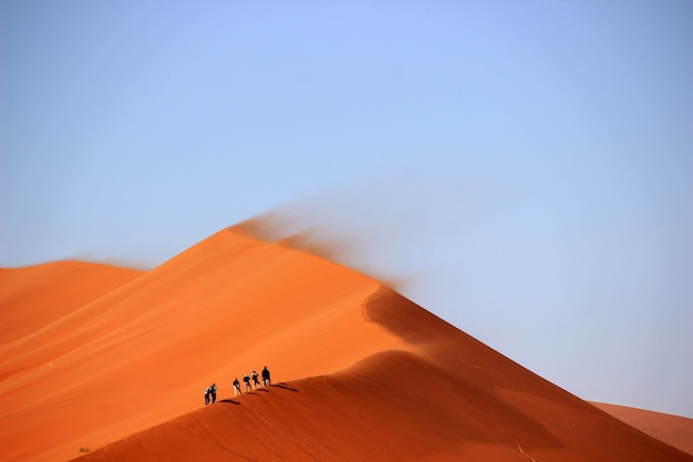 Toeristen beklimmen de zandduinen in de woestijn met de blauwe lucht