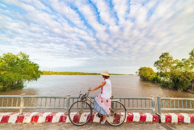 Toeristen berijdende fiets in het mekong deltagebied, ben tre, zuid-vietnam. vrouw die pret het cirkelen onder waterkanalen heeft