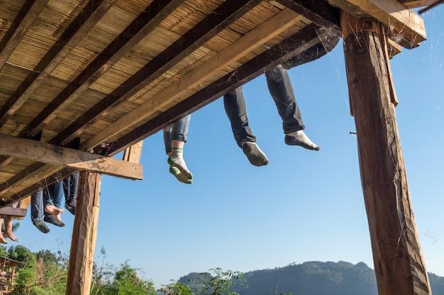 Toeristen die benen zitten die op terras hangen